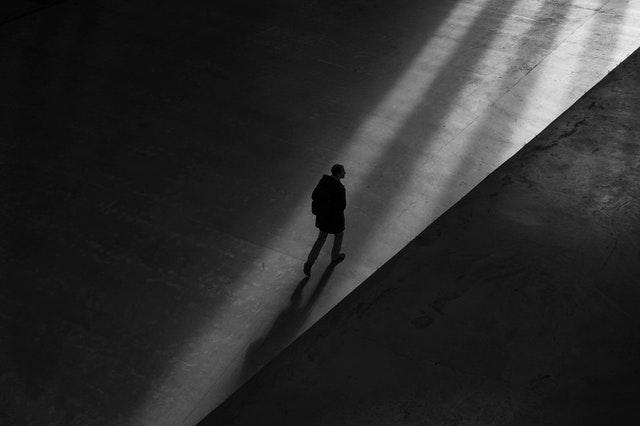 person walking in shadows